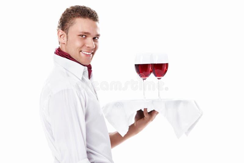 El camarero joven con una bandeja foto de archivo