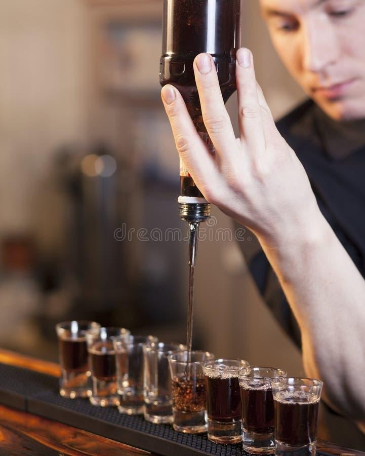 El camarero llena algunos vidrios en una fila foto de archivo libre de regalías