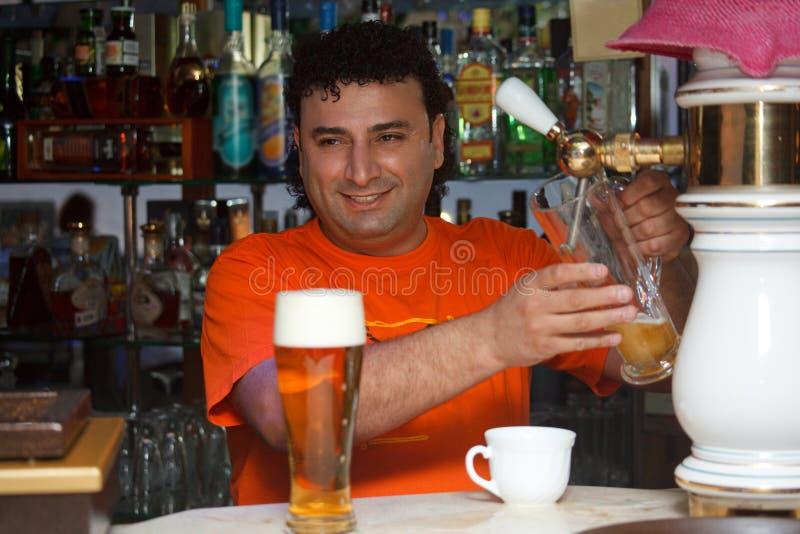 El camarero llena el vidrio de cerveza imagen de archivo libre de regalías
