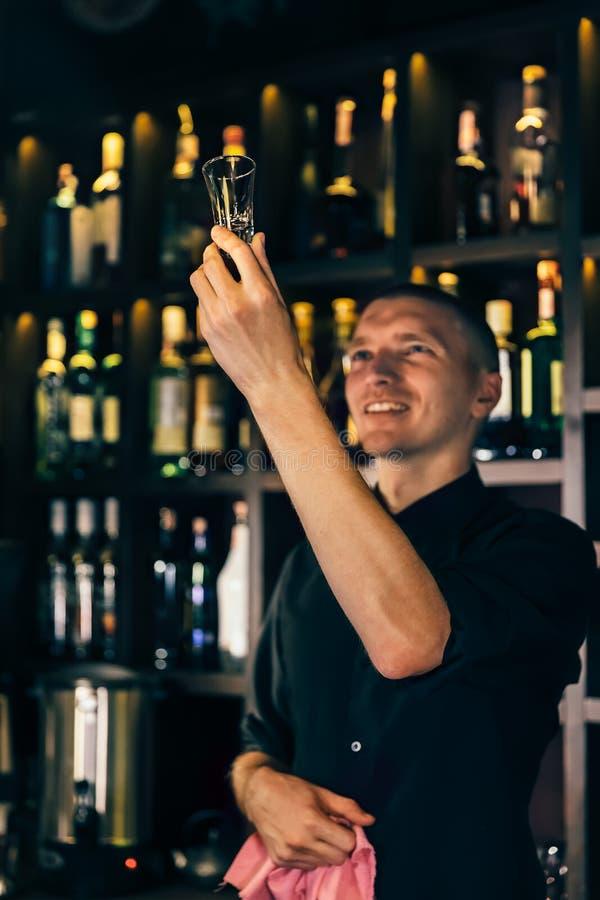 El camarero mira un cristal El camarero que limpia el vidrio en la barra foto de archivo libre de regalías