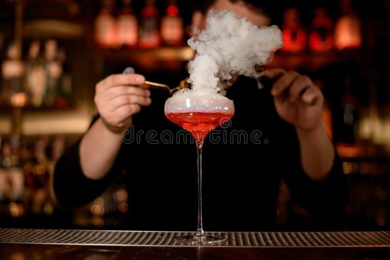 El camarero pone espuma en una bebida del alcohol foto de archivo libre de regalías
