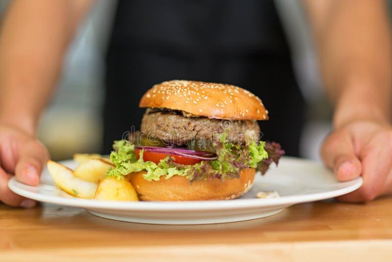 El camarero sirve la hamburguesa foto de archivo
