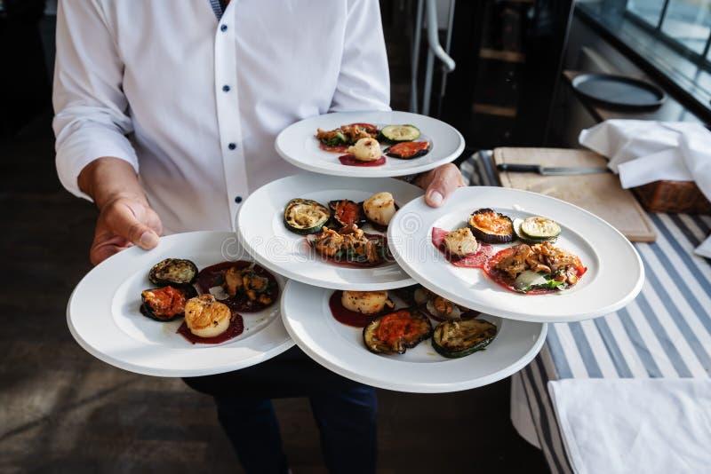El camarero sirve los antipasti italianos en un restaurante al aire libre fotografía de archivo