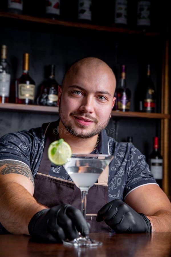 El camarero sostiene hacia fuera los cócteles al cliente en la barra en restaurante Bienvenido foto de archivo
