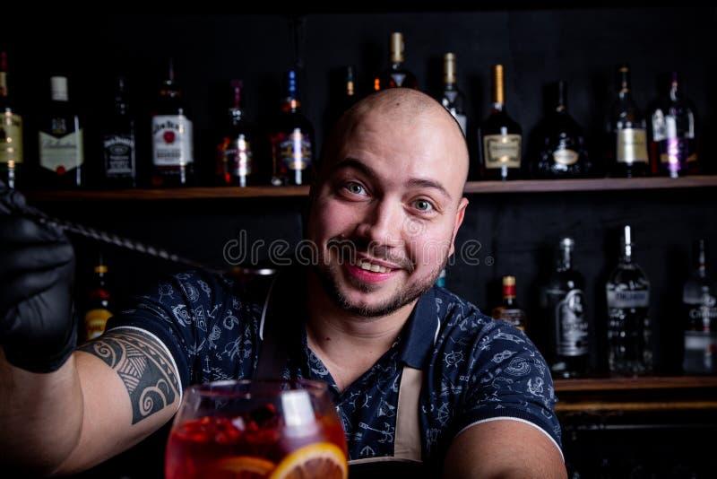 El camarero sostiene hacia fuera los cócteles al cliente en la barra en restaurante Bienvenido fotos de archivo