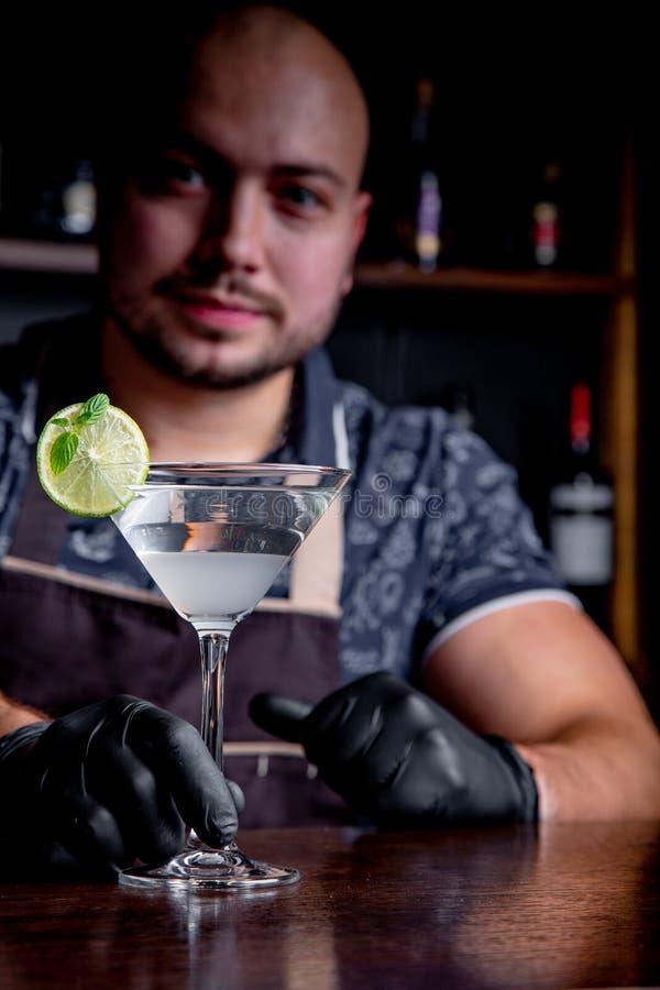 El camarero sostiene hacia fuera los cócteles al cliente en la barra en restaurante Bienvenido imagenes de archivo