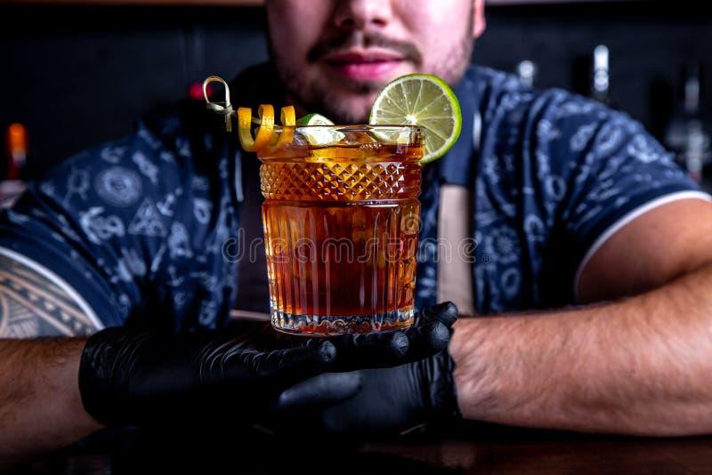 El camarero sostiene hacia fuera los cócteles al cliente en la barra en restaurante Bienvenido imagen de archivo
