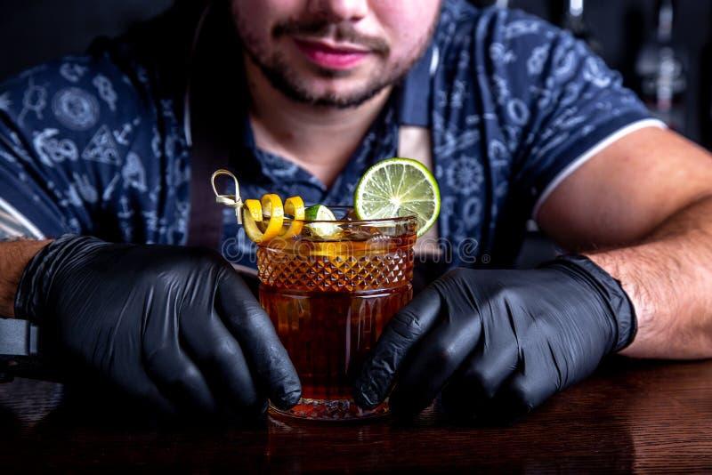 El camarero sostiene hacia fuera los cócteles al cliente en la barra en restaurante Bienvenido foto de archivo libre de regalías