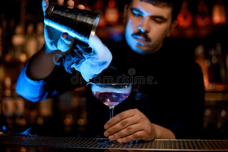El camarero utiliza la coctelera para verter un cóctel del alcohol foto de archivo libre de regalías
