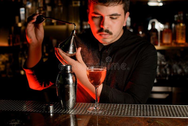 El camarero utiliza el pulverizador para hacer un cóctel foto de archivo