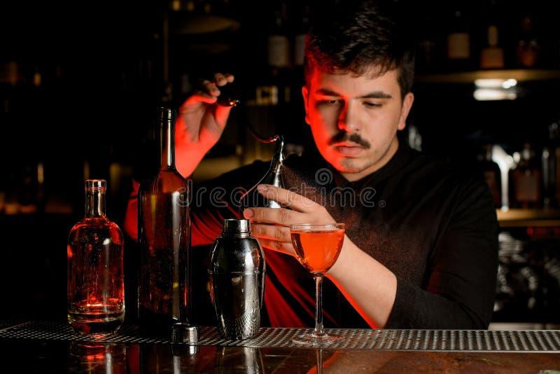 El camarero utiliza el rociador para hacer un cóctel foto de archivo