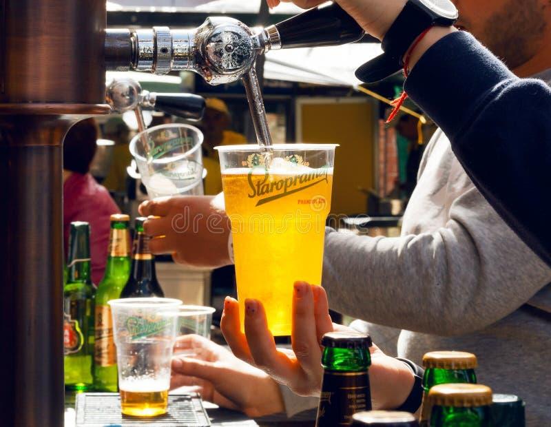 El camarero vierte la cerveza en vidrio plástico durante festival de la comida de la calle fotografía de archivo