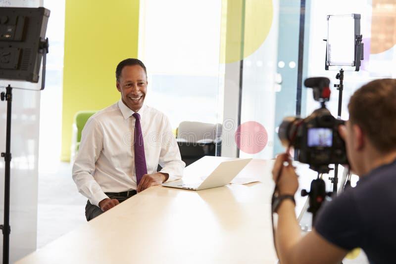 El cameraman y el centro envejecieron al hombre de negocios que hacía el vídeo corporativo imagen de archivo libre de regalías