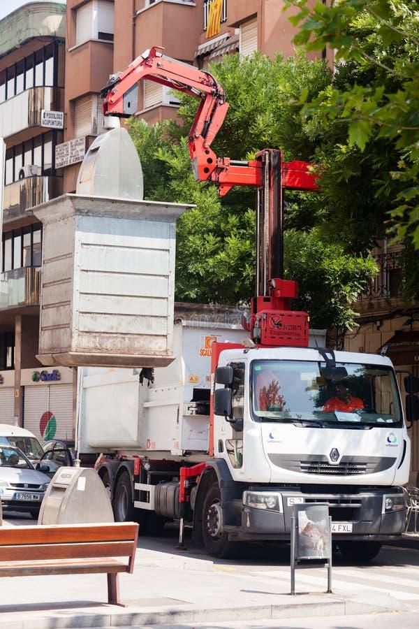 El camión de basura recoge los cubos de la basura foto de archivo