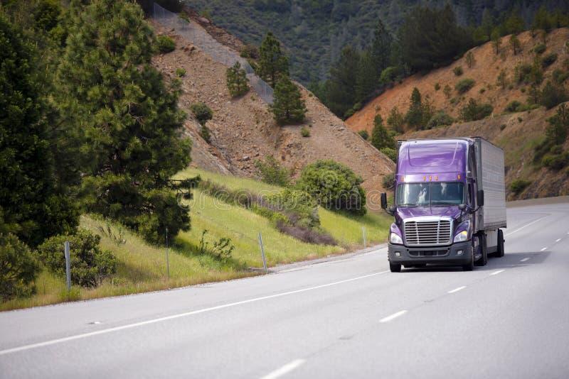 El camión de la lila semi con el remolque de aluminio se está moviendo a lo largo de enrollar h fotos de archivo libres de regalías