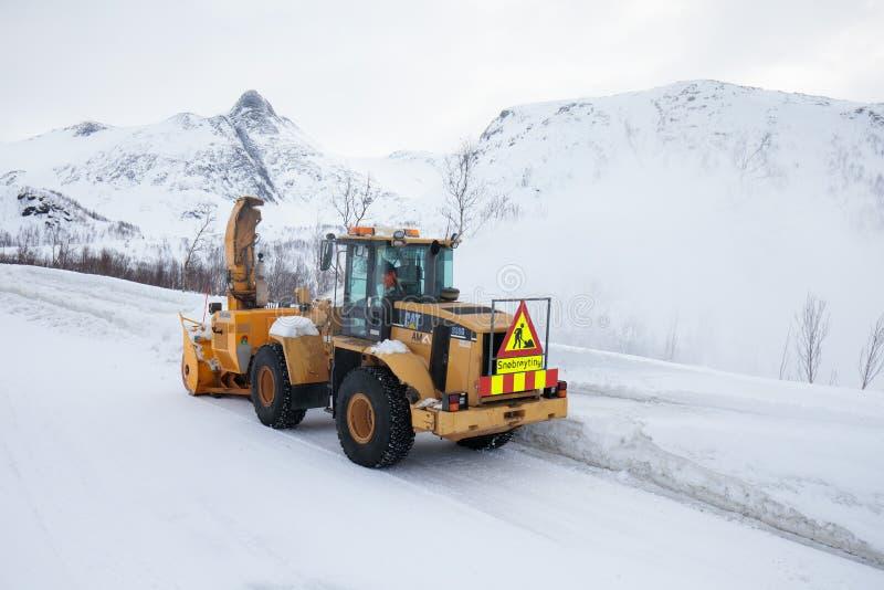 El camión del quitanieves que despeja el camino helado después de la ventisca de la nevada del invierno para el ventilador de n imágenes de archivo libres de regalías