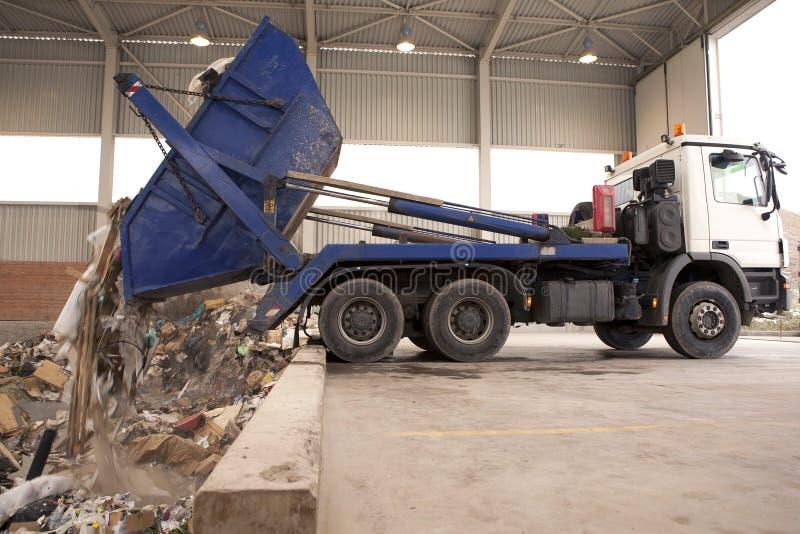 El camión descarga la basura al incinerador, agujero donde el gancho agarrador grande tomar los desperdicios y ponerlos en el fue foto de archivo