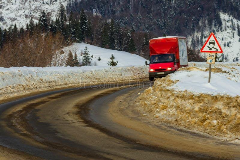 El camión monta en una sección peligrosa del camino entre nieve en imagen de archivo libre de regalías