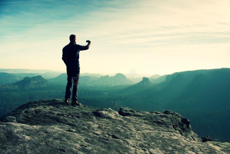 El caminante alto está tomando la foto por el teléfono elegante en el pico de la montaña en la salida del sol imagen de archivo libre de regalías