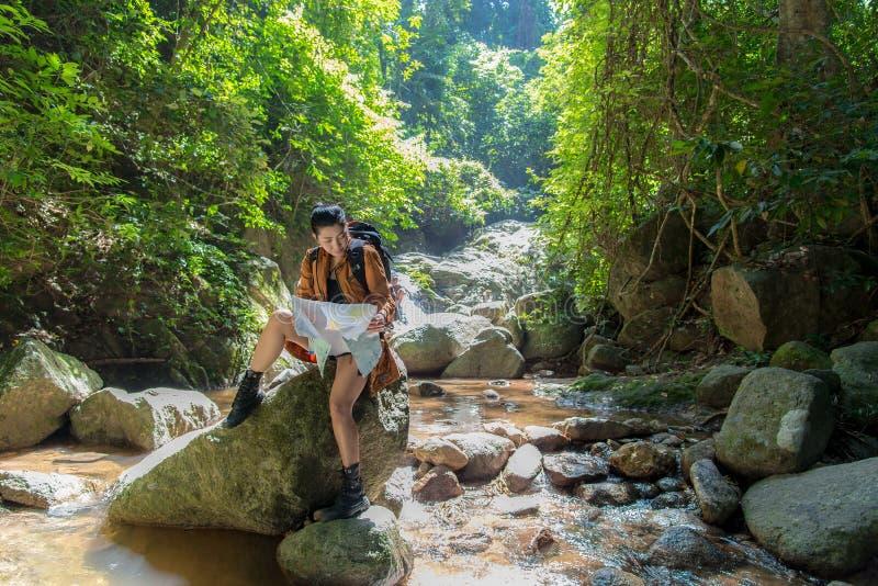 El caminante asiático de las mujeres con los controles de la mochila traza para encontrar direcciones en área silvestre en las ca foto de archivo