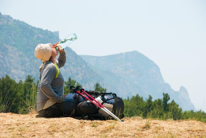 El caminante cansado bebe el agua fotografía de archivo libre de regalías