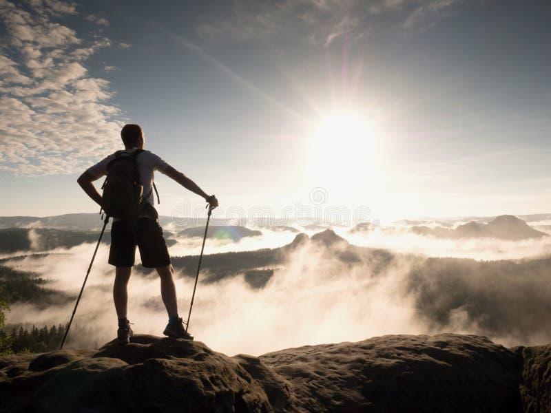 El caminante con la mochila alcanza la cumbre del pico de montaña Éxito, libertad y felicidad, imágenes de archivo libres de regalías