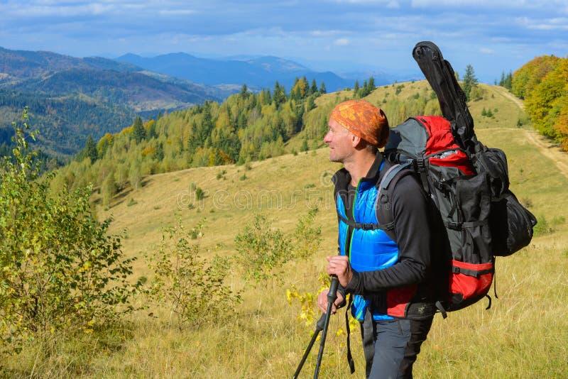 El caminante con la mochila es reclinación, disfrutando de paisaje en el autum imagen de archivo