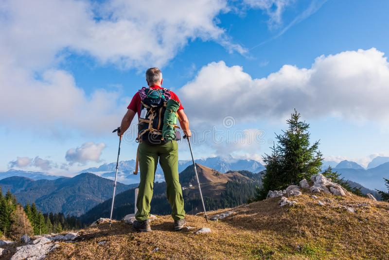 El caminante con la mochila es soporte en el top de la montaña imagenes de archivo
