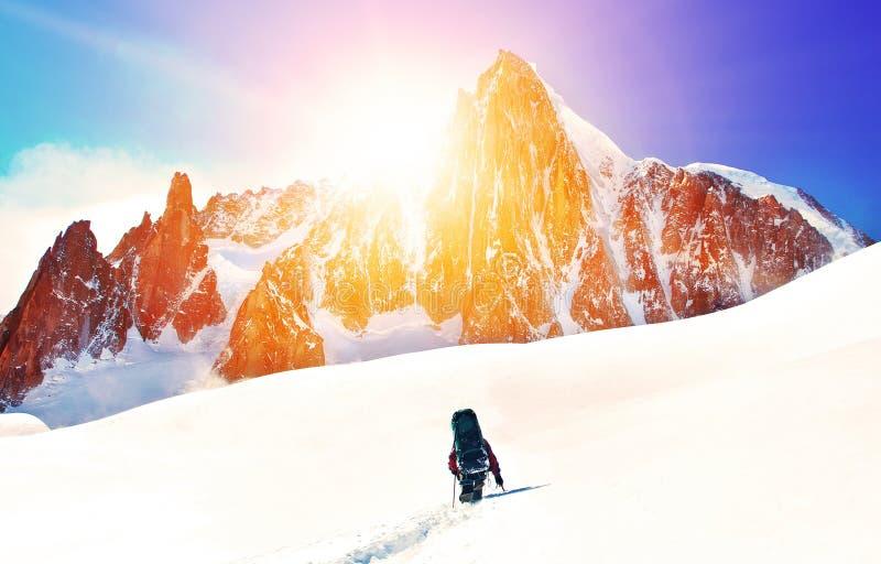 El caminante con las mochilas alcanza la cumbre del pico de montaña Libertad del éxito y logro de la felicidad en montañas Estafa foto de archivo libre de regalías