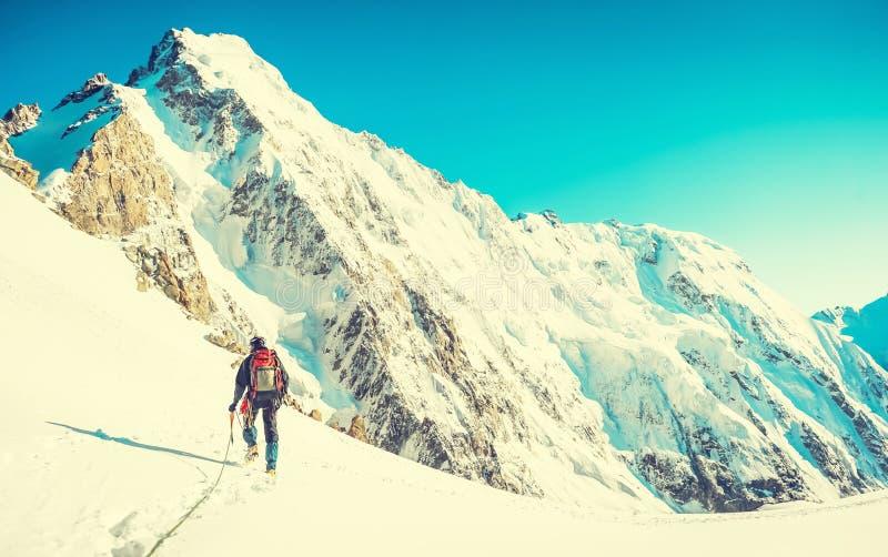 El caminante con las mochilas alcanza la cumbre del pico de montaña Libertad del éxito y logro de la felicidad en montañas Estafa imagen de archivo