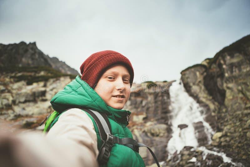 El caminante de la montaña del muchacho invita alguien a caminar con él a la cascada fotografía de archivo