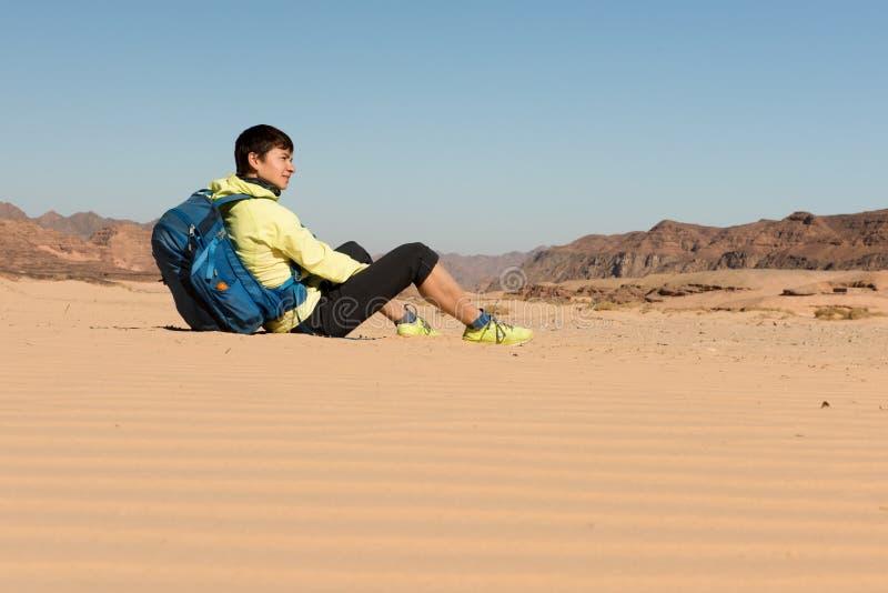 El caminante de la mujer con la mochila disfruta de la visión en desierto imagen de archivo