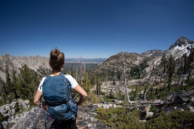El caminante de la mujer del Backpacker se coloca al borde de una roca en bosque del Estado del diente de sierra fotografía de archivo libre de regalías