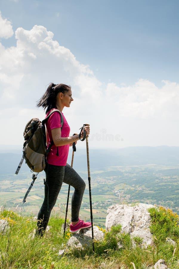 El caminante de la mujer joven se coloca en un pico de montaña sobre el valle foto de archivo