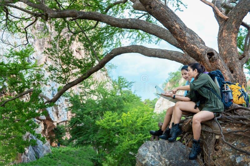El caminante de las mujeres del grupo con la mochila en controles grandes del árbol traza para encontrar direcciones y para mirar fotografía de archivo libre de regalías