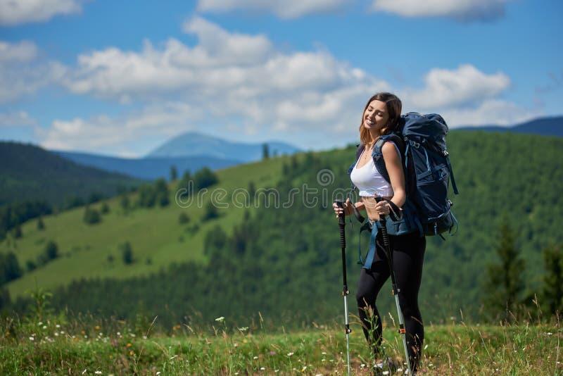 El caminante deportivo de la mujer con la mochila y el senderismo pega caminar en las montañas imagen de archivo libre de regalías