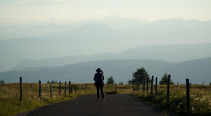 El caminante disfruta de la opinión sobre las montañas de la dolomía en la puesta del sol imagenes de archivo