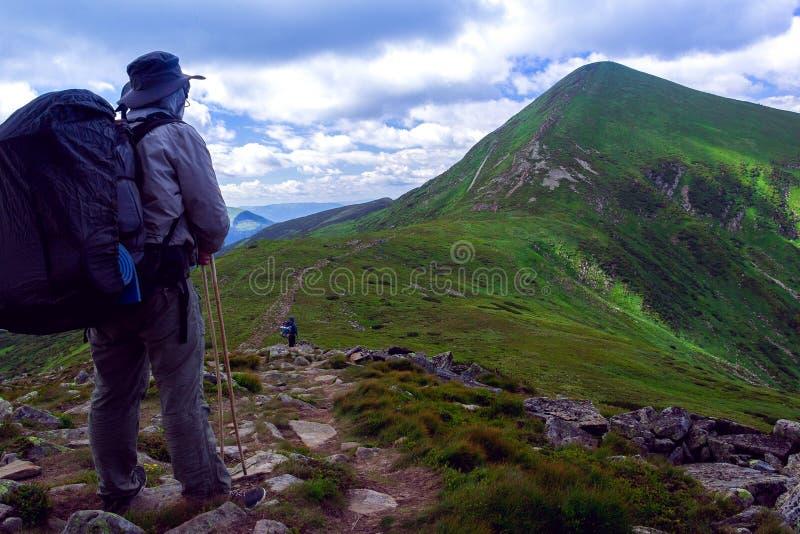 El caminante es soporte y mirada lejos a las montañas foto de archivo libre de regalías