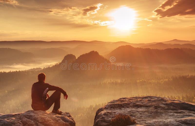 El caminante está disfrutando de la opinión de la salida del sol en paisaje montañoso Sentada masculina del caminante fotos de archivo