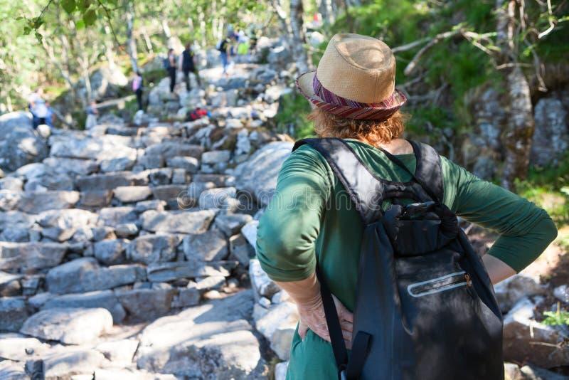 El caminante europeo maduro de la mujer que considera adelante la manera de piedra, mochila es encendido trasero fotos de archivo libres de regalías