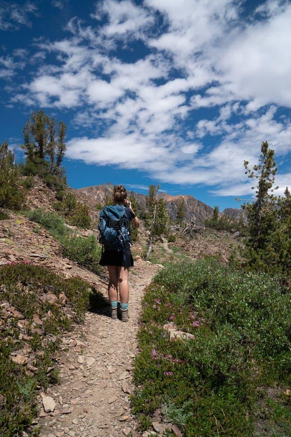El caminante femenino hermoso del backpacker toma las fotos a lo largo del rastro fotografía de archivo