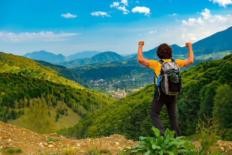 El caminante joven de la montaña con los brazos aumentó para arriba, celebrando y disfrutando de un paisaje hermoso de la montaña foto de archivo libre de regalías
