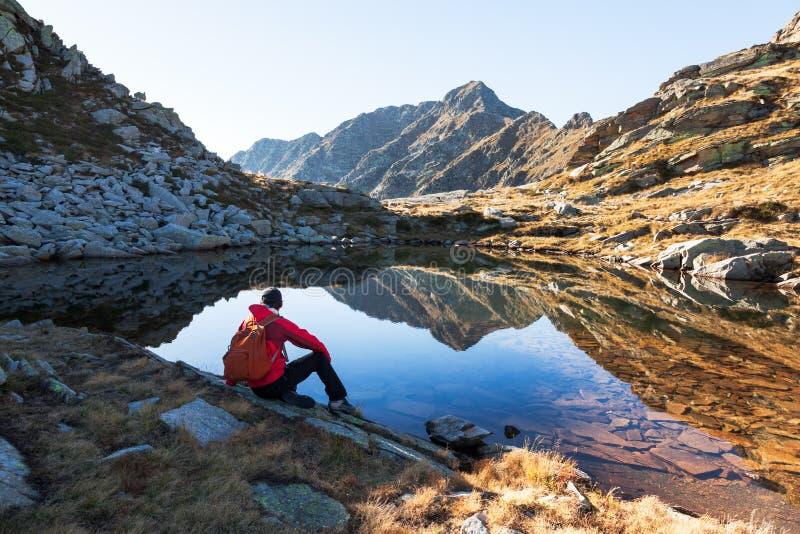 El caminante masculino toma un resto que sienta después un lago de la montaña fotografía de archivo libre de regalías