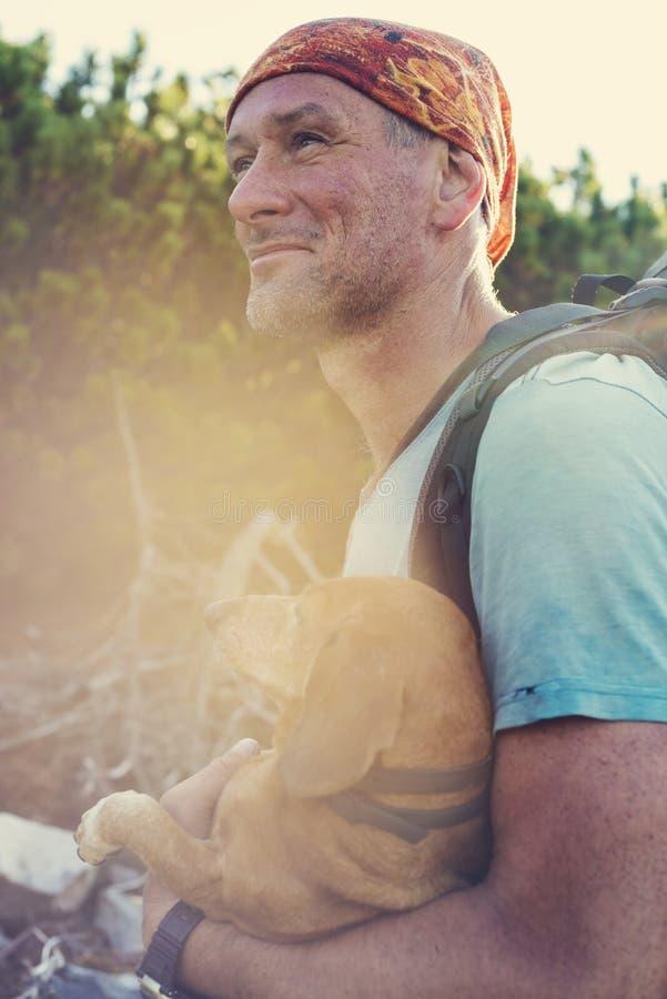 El caminante se coloca en un rastro de montaña con un pequeño perro divertido imagen de archivo libre de regalías