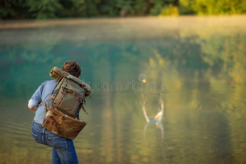 El caminante se está divirtiendo en el banco del río fotografía de archivo