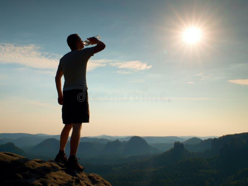 El caminante sediento en pantalones negros bebe de la botella de agua Turista cansado sudoroso en el pico del parque rocoso Sajon fotografía de archivo libre de regalías