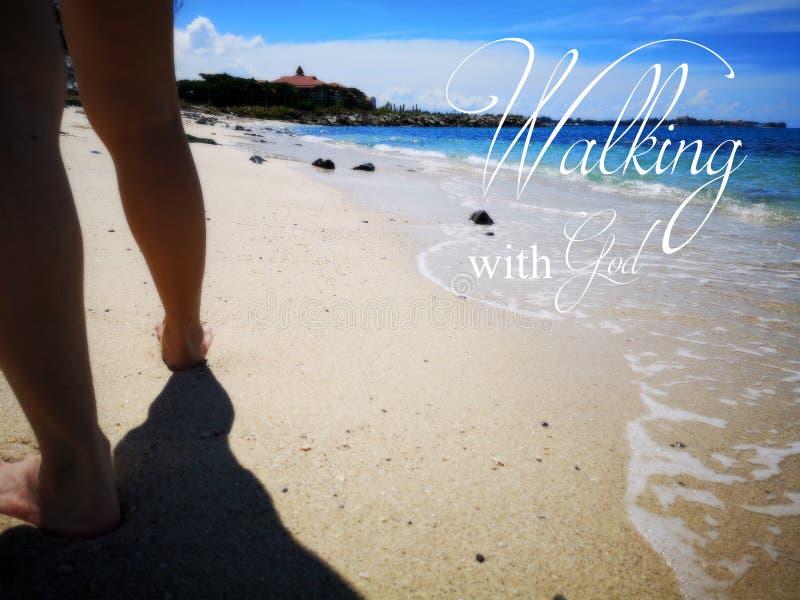 El caminar con dios con vista al mar del fondo y una señora que camina descalzo en el diseño de la playa arenosa para el cristian foto de archivo libre de regalías