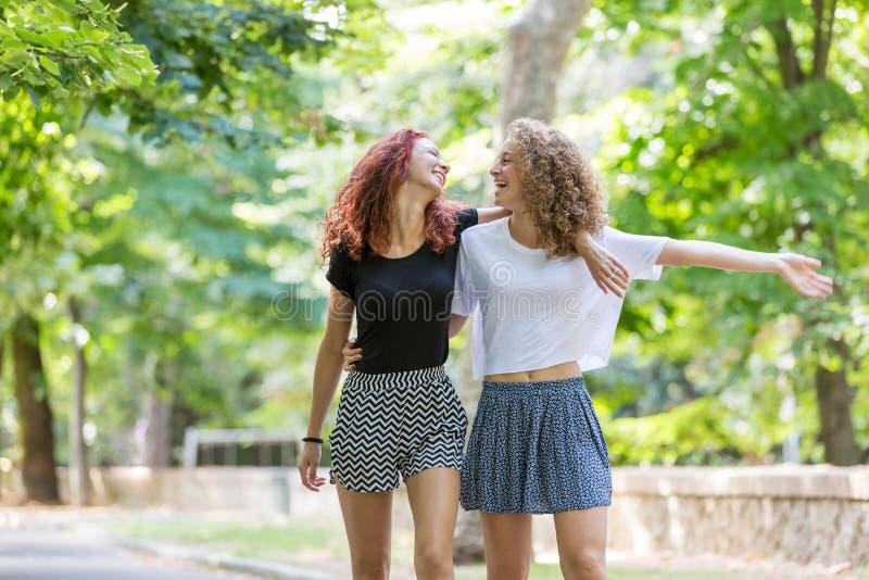 El caminar de dos muchachas abrazado en el parque foto de archivo