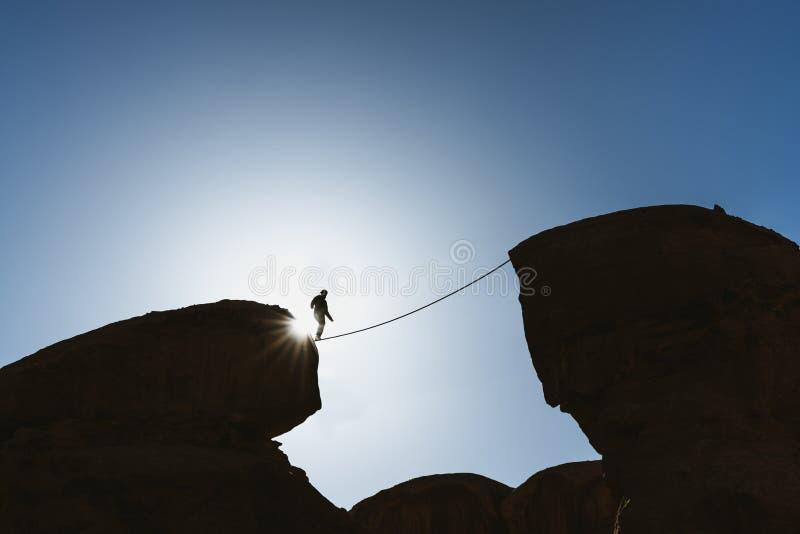 El caminar de equilibrio del hombre en cuerda sobre precipicio Negocio, asunción de riesgos, desafío, valor, y concentración fotografía de archivo