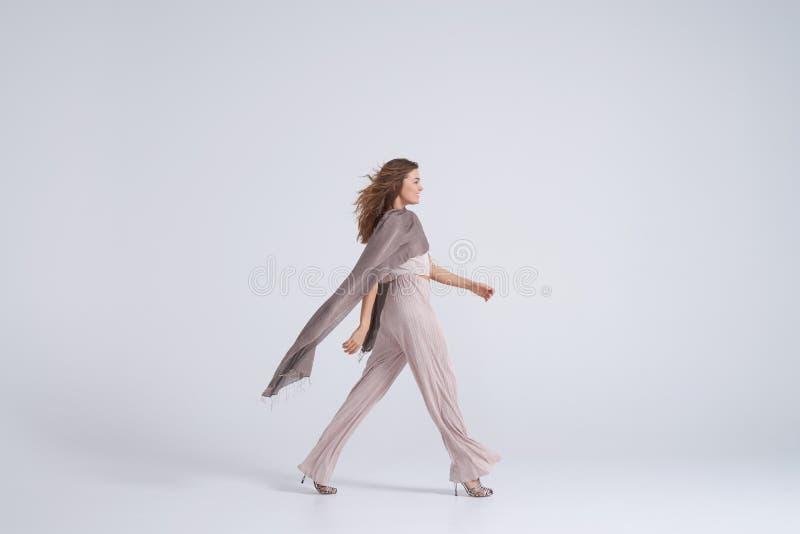 El caminar de la bufanda de la ropa y de la seda de la tendencia de la mujer que lleva fotografía de archivo libre de regalías